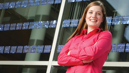 Sustainable business student in front or Lillis Business Complex solar glass