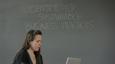 Female MBA student works on a laptop in front of a chalk board with the words Center for Sustainable Business Practices