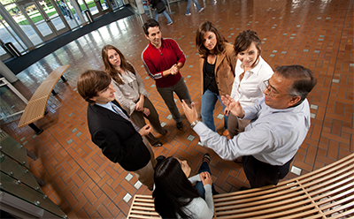 Students faculty and alumni of the Center for Sustainable Busienss Practices chat in a circle in the Lillis Complex atrium