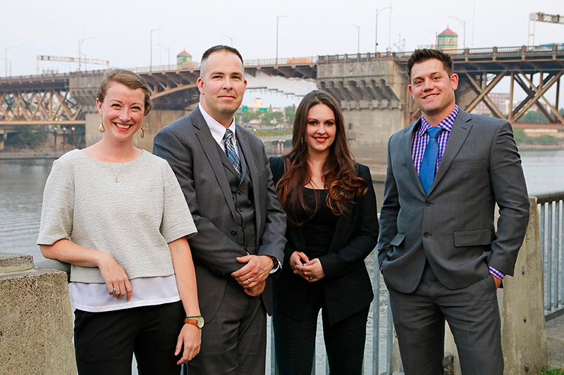 Four executive MBA students stand in front of the Burnside Bridge in Portland
