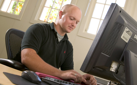 Oregon MBA student entering data on a computer