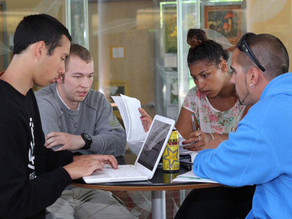 A group of students study intently in the Lillis atrium at the University of Oregon