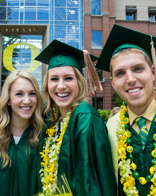 Students pose in front of the Lillis O during commencement ceremonies