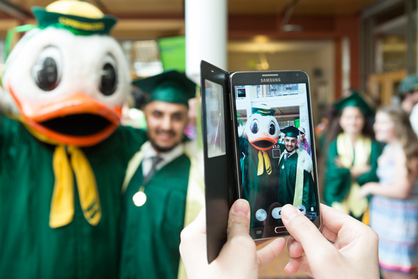 Photo of a student being photographed with cell phone during the Lillis commencement reception