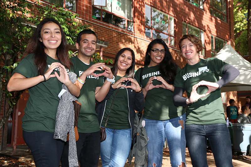 Business students make the Oregon O with their hands