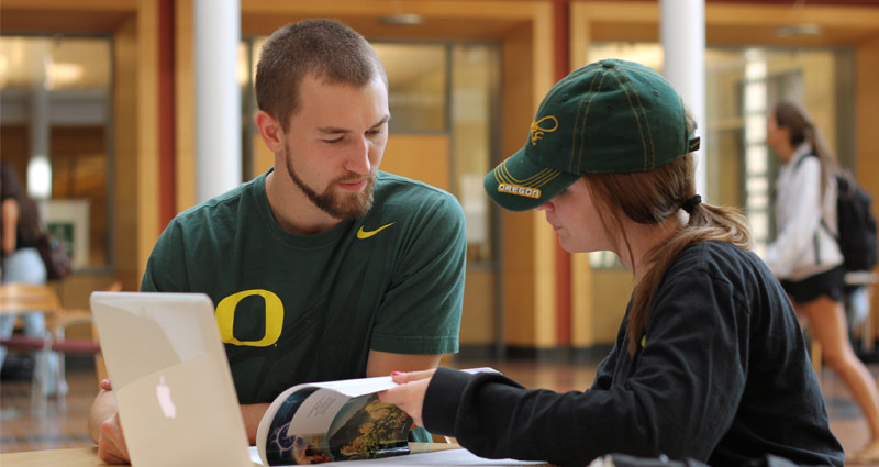 Two students study in the Lillis atrium