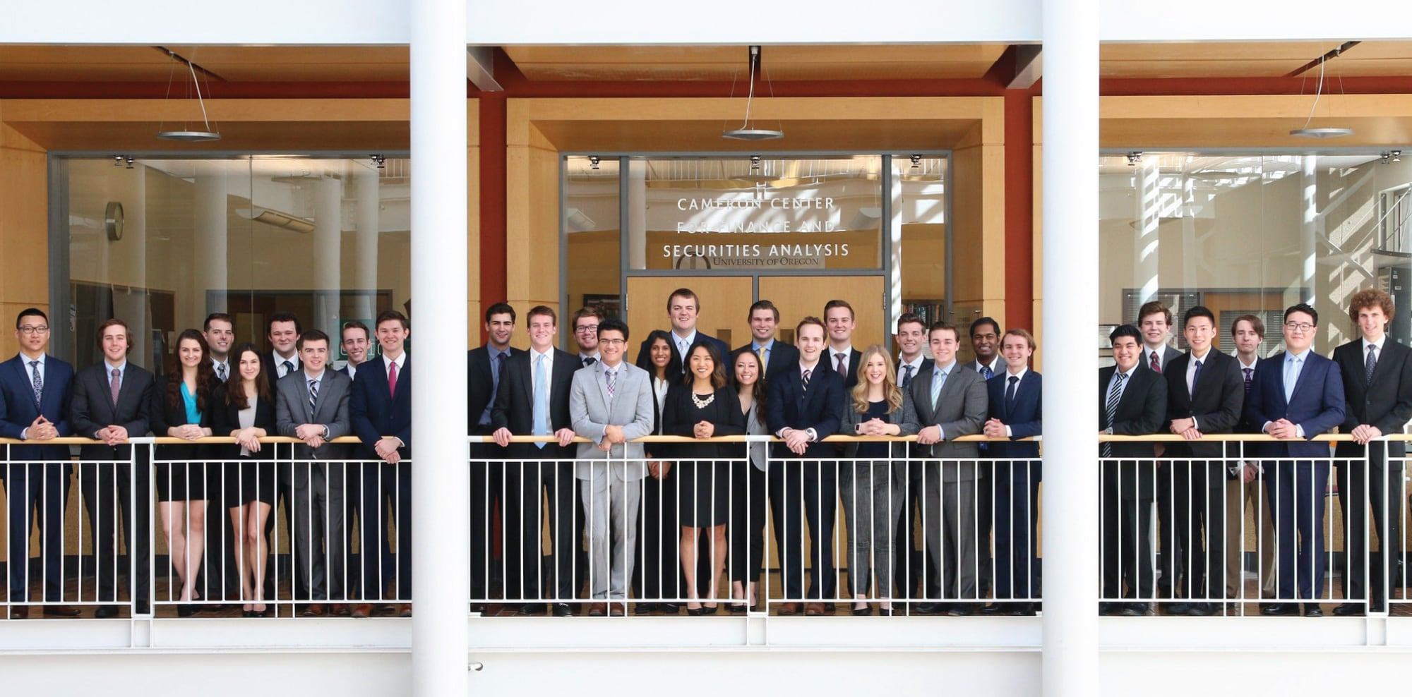 Large gathering of UO Investment Group students stand in front of the Cameron Center for Finance and Securities Analysis in the Lillis Business Complex.