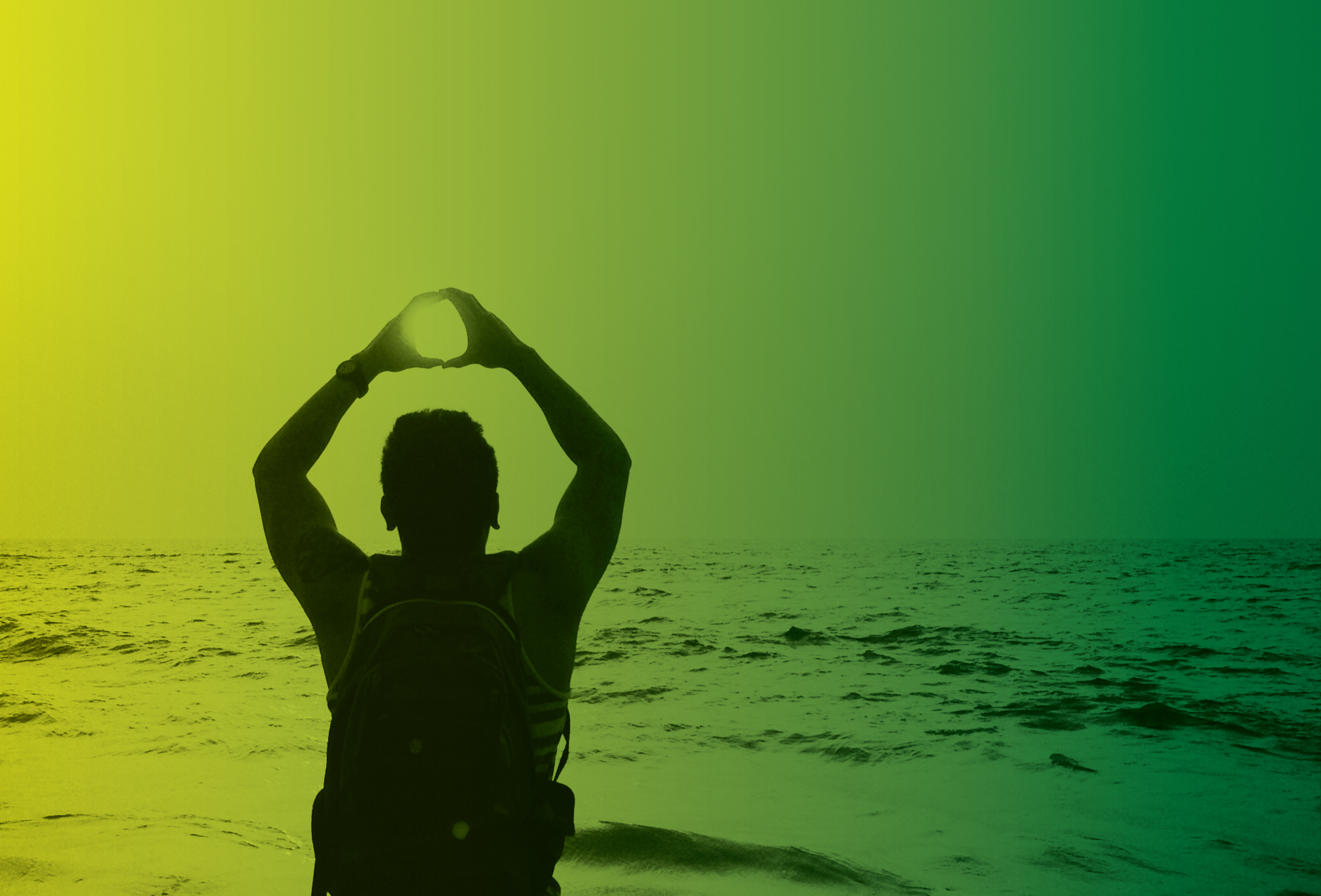 A person makes the O symbol with their hands against a backdrop of the ocean
