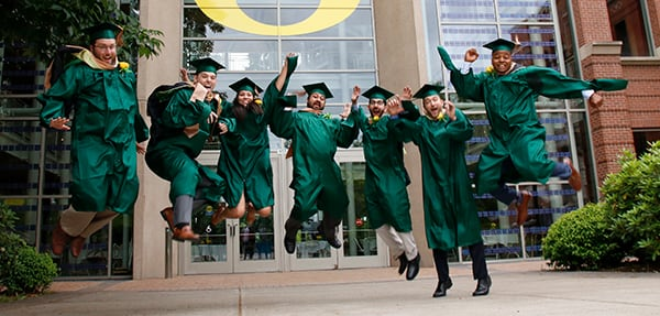 Graduates in regalia jump in front of the Lillis Business Complex