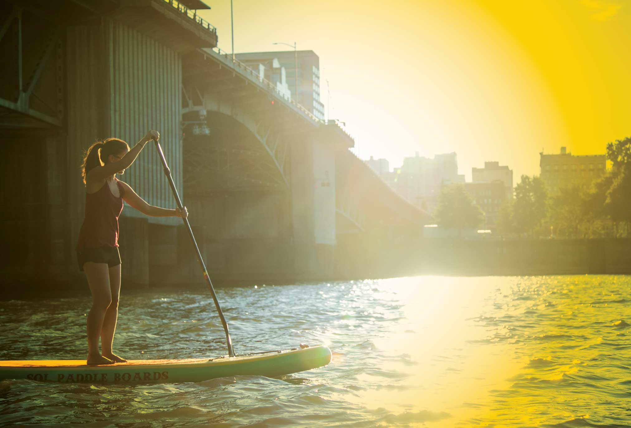 A woman paddles underneath a bridge in the Columbia River in Portland