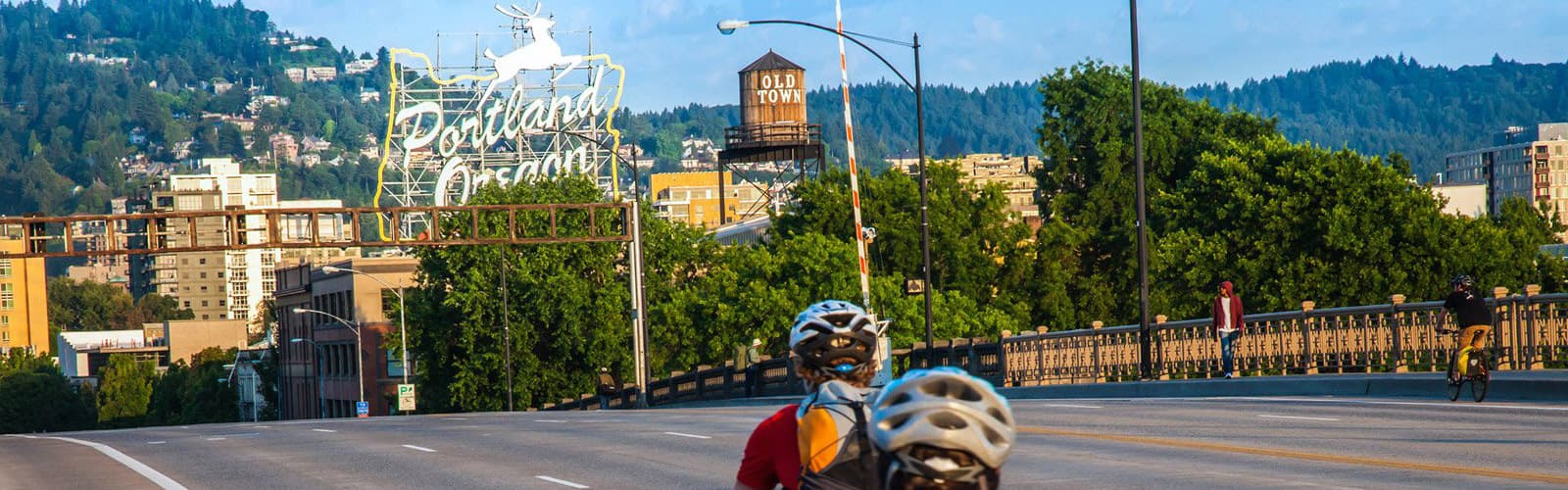 Bikers on the Burnside Bridge going toward the Portland sign