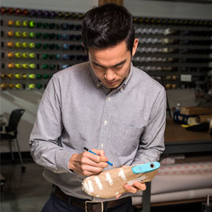 A student sketches designs on a shoe mold