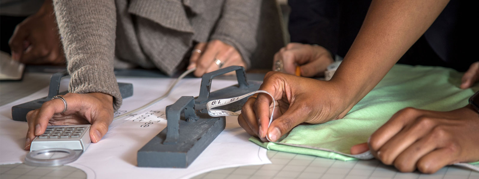 Close-up shot of students measuring material in workshop