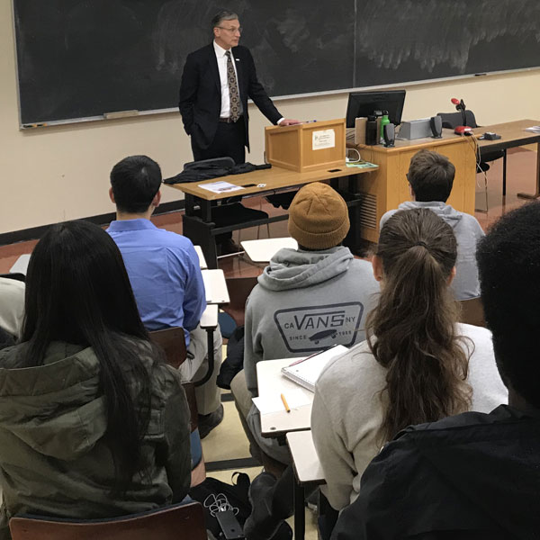 A speaker addresses a group of students