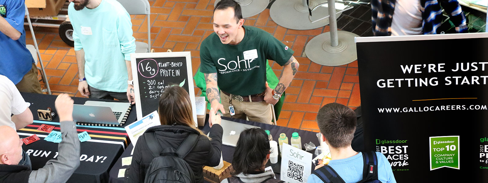 Alumni startup owner shakes hands with student