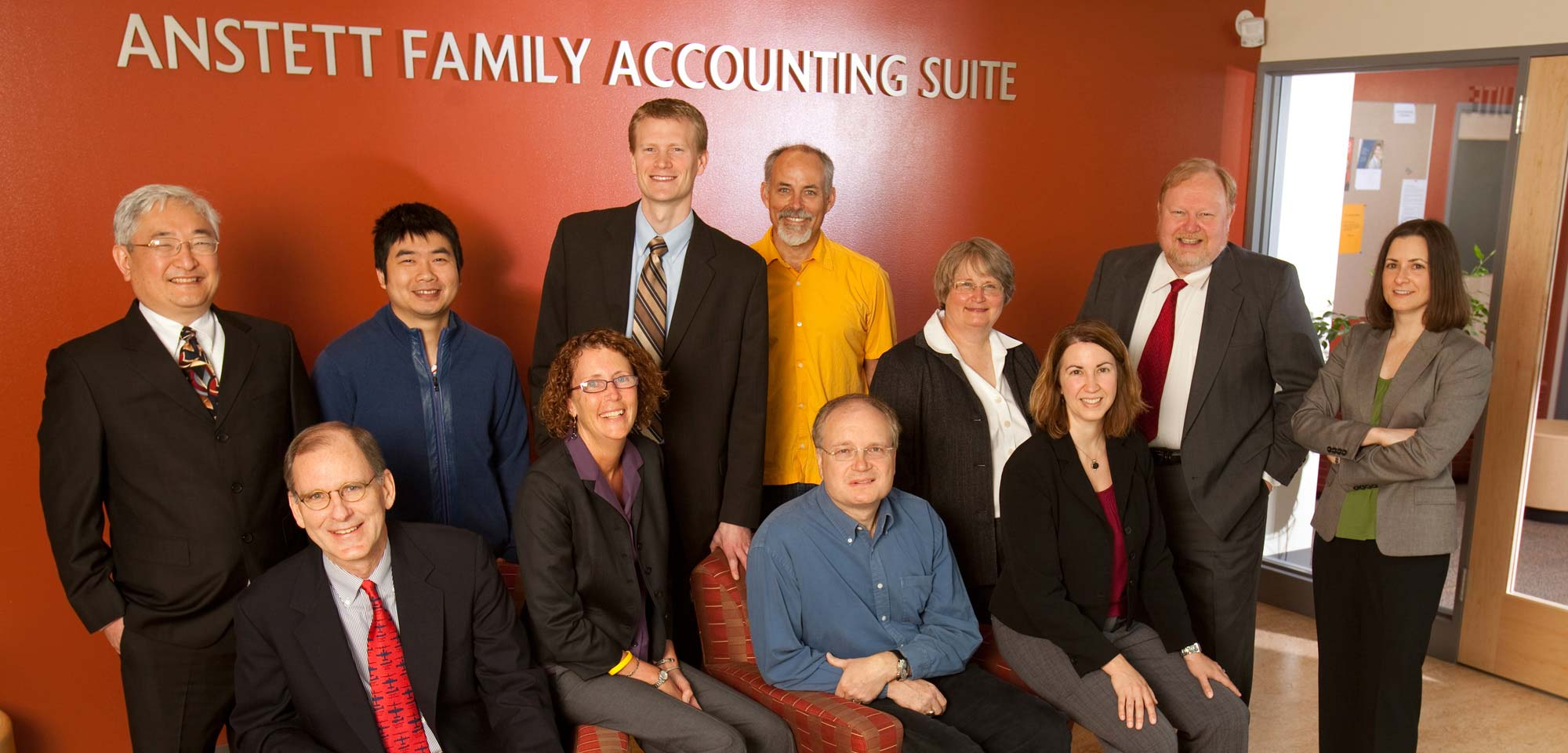 Accounting staff pose in a group in front of the accounting suite