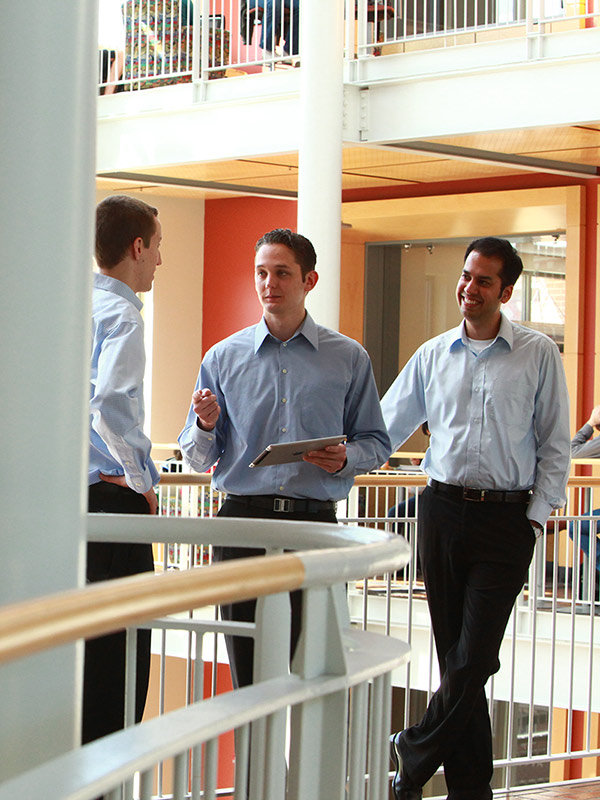 Three students discuss a project in the Lillis atrium