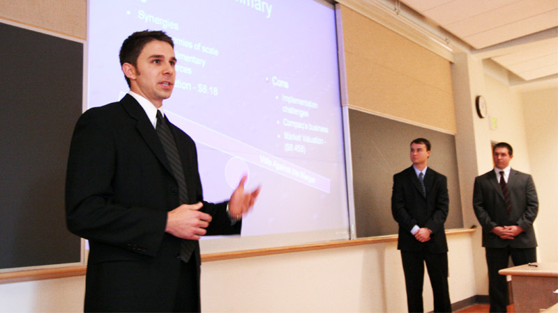 Three MBA students present their research to an audience