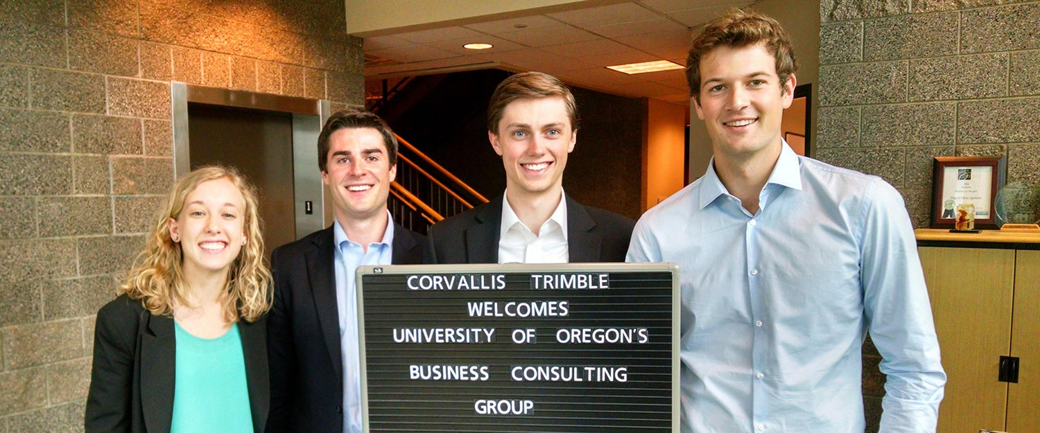 OBCG students pose behind a sign welcoming them to Corvallis Trimble