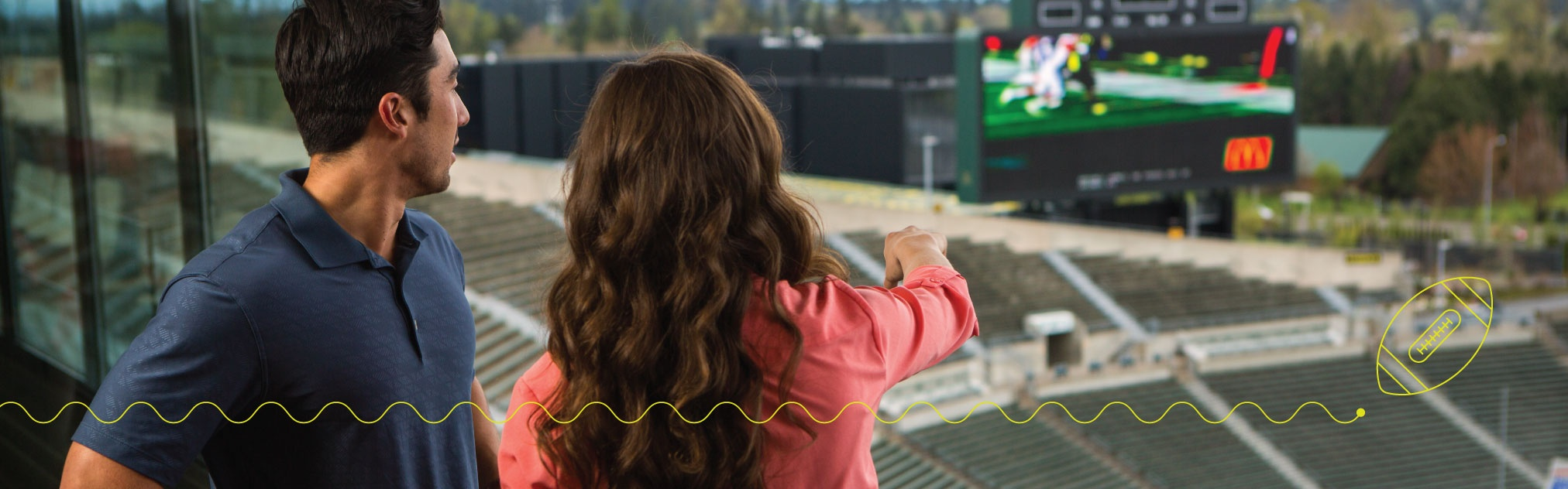 Two young people look out over a football field