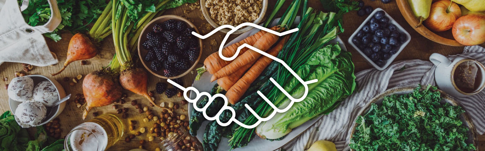 White lineart icon of two shaking hands against a backdrop of various produce