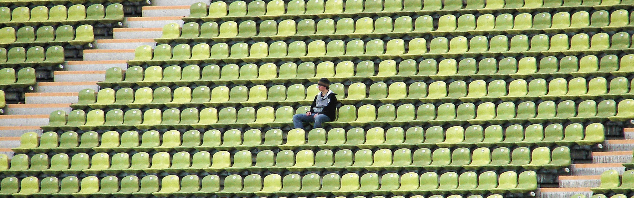 A fan sits alone in a stadium