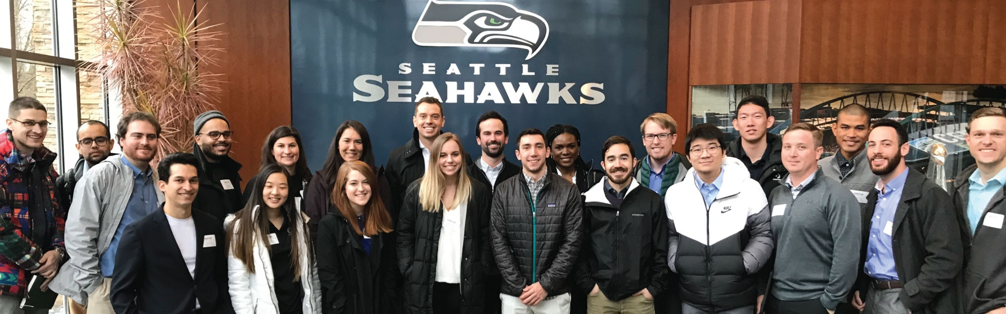 MBA students take a group photo in front of the Seattle Seahawks logo