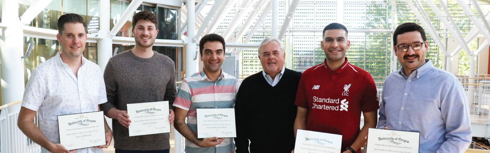 Roger Best poses for a photo with award-winning PhD students