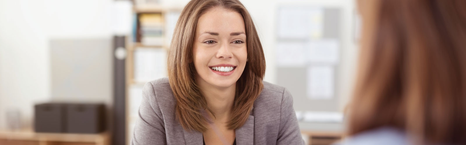 A person in business attire smiles at another who is not facing the camera