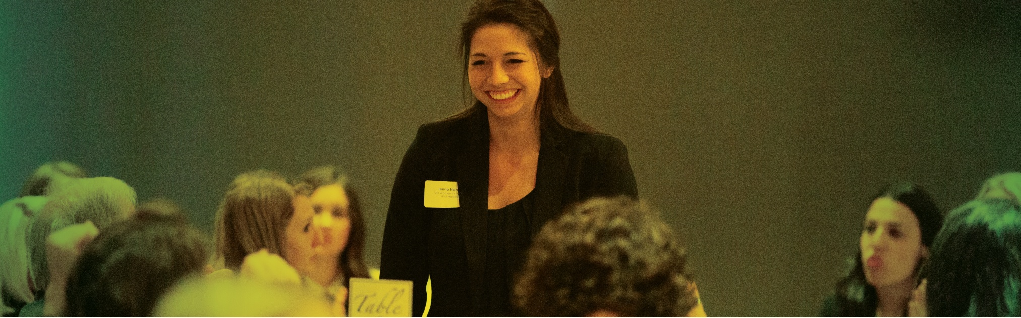 A student rises from her table at the Women in Business gala