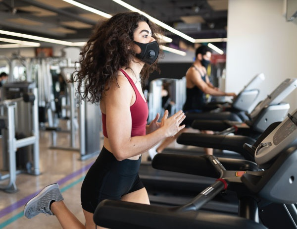 A person exercises on a gym treadmill while wearing a mask