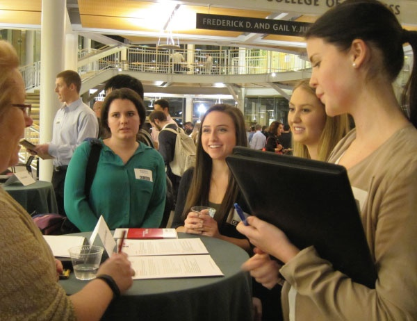 Students network with banking professionals during an event in the Lillis atrium