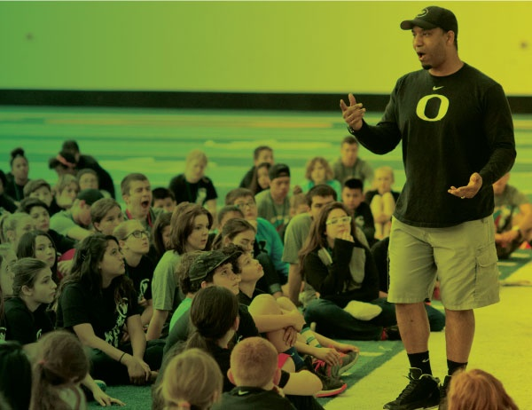 An instructor speaks before a group of young students
