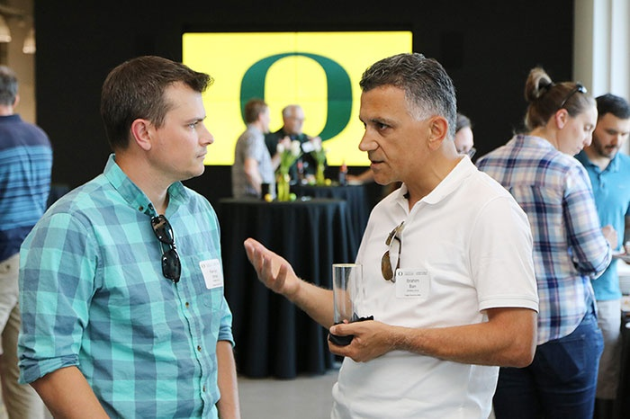 Two alumni talk with each other at a recent gathering in the program's Naito Parkway facility in Portland.