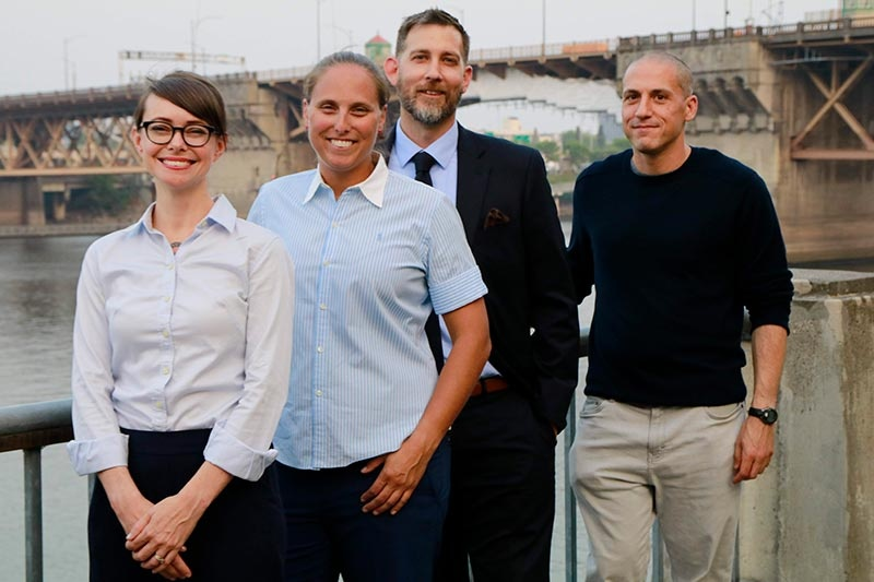 Four executive MBA students stand in front of Portland's Burnside Bridge.