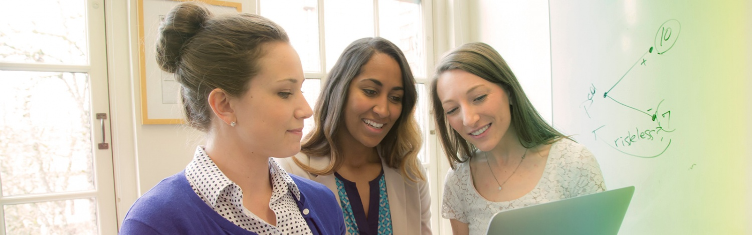 MBA students look over work together