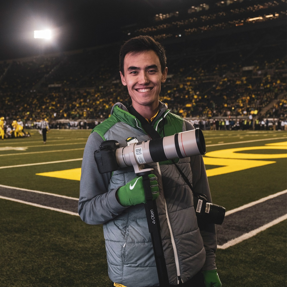 Mark Nelson holds a camera on the Autzen Stadium field