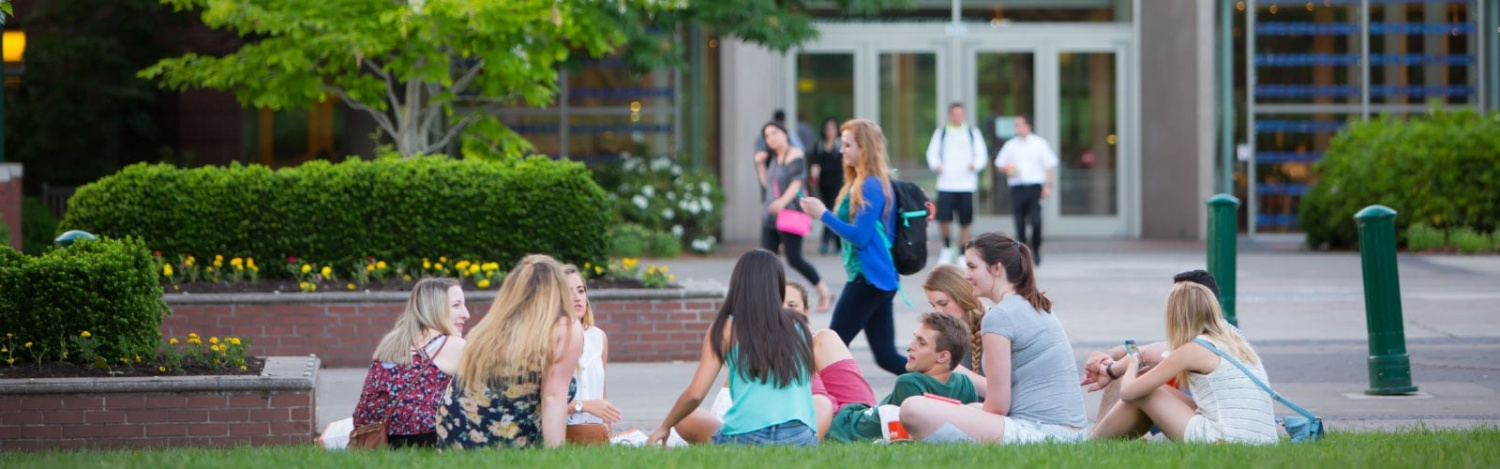 Students sit in a circle studying on the memorial lawn in front of the Lillis Business Complex