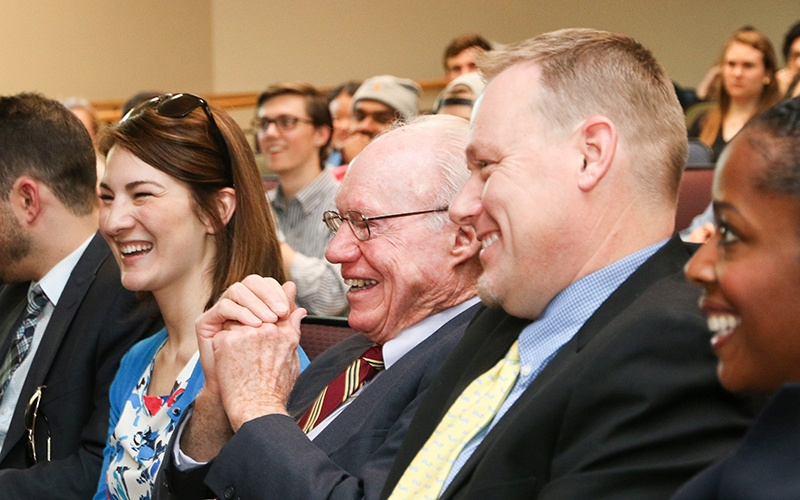 Donors, alumni, and community members smiling and enjoying a light moment while attending a lecture at the Lundquist College