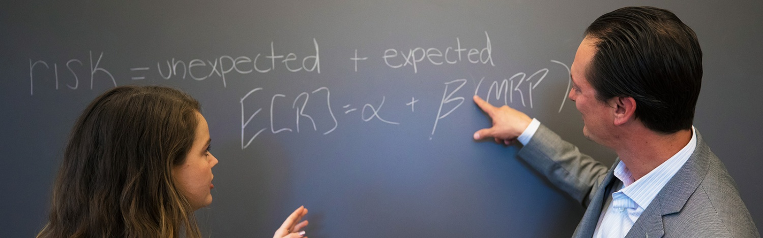 A professor explains an equation on a chalkboard to a student