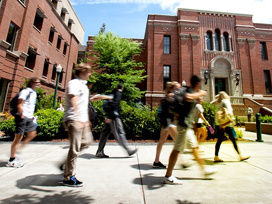Undergraduate students walking outside in front of the Lillis Business Complex in motion