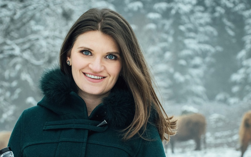 Photo of MBA alumni Emily Darchuk in the snow with cows behind her signifying her startup Wheyward Spirit