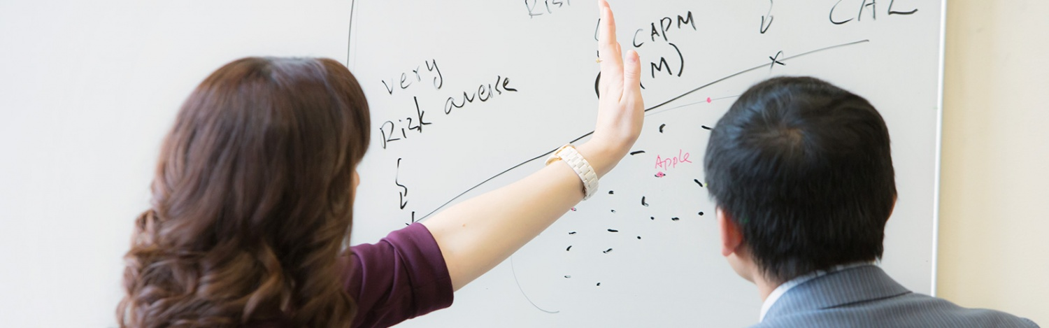 An MBA student discusses an equation with a professor