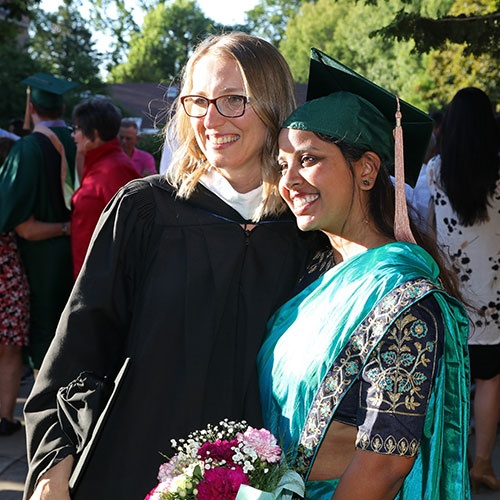 An Oregon MBA student celebrates with her advisor at the graduation ceremony
