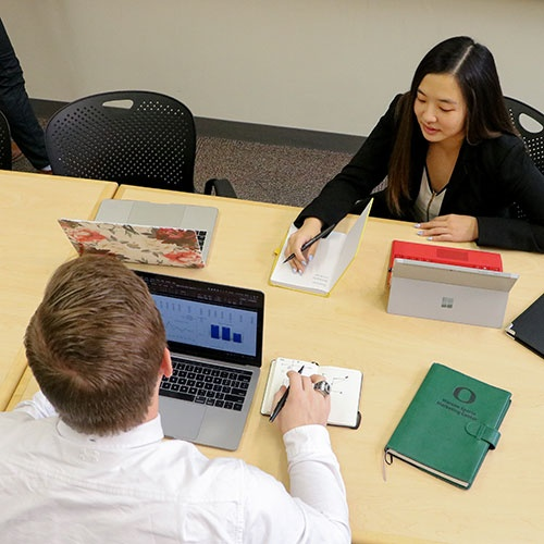 Photo taken from above looking down an a table as Oregon MBA students work diligently