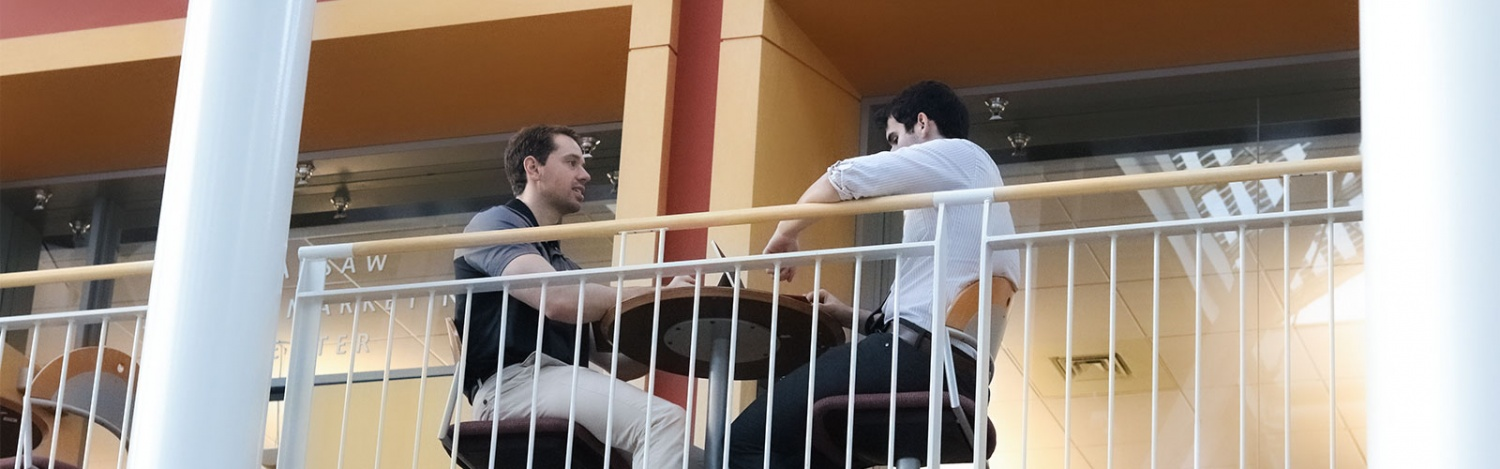 MBA students sit in the atrium in the Lillis Business Complex in front of the Warsaw Sports Marketing Center and study