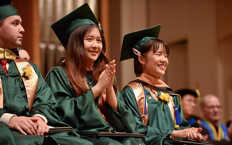 MS Finance students on stage during commencement at the University of Oregon