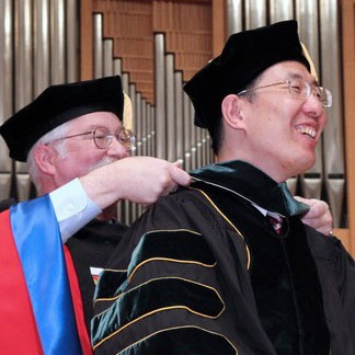 A PhD student has regalia placed around their neck by a professor