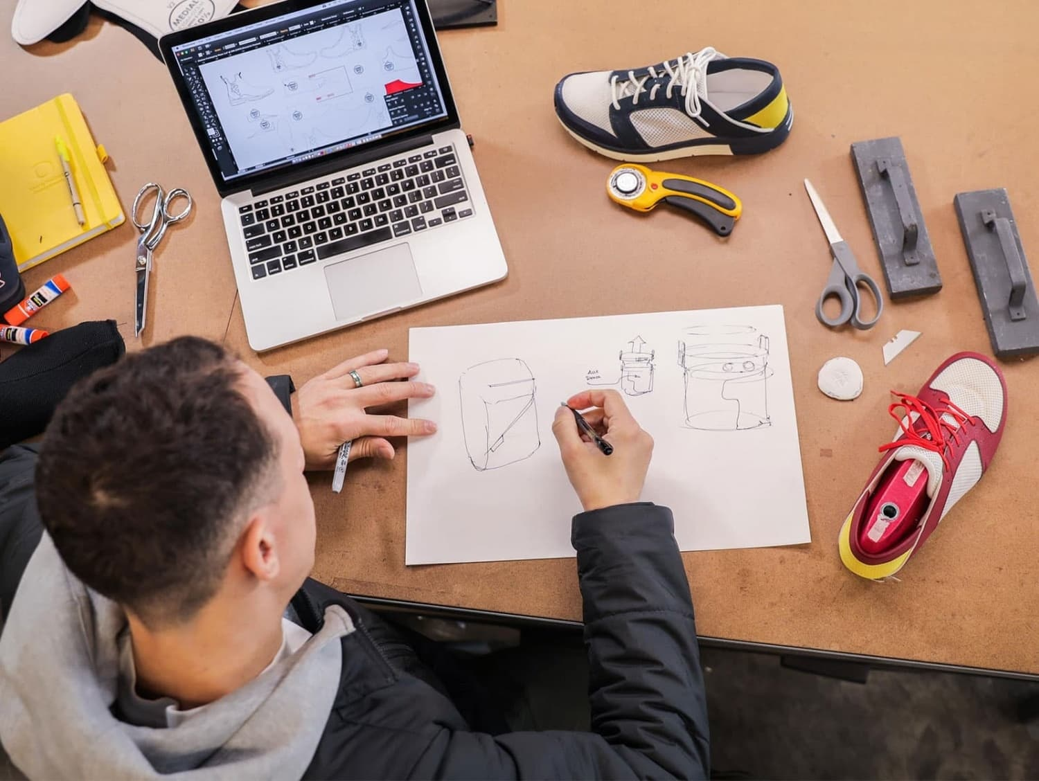 Sports Product Management students sketches a backpack on a work surface with shoes, cutting supplies, and a laptop