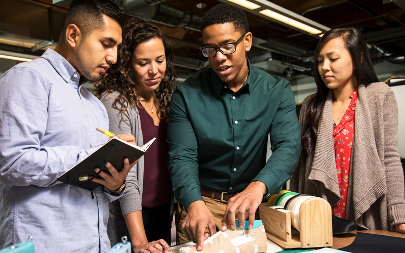 Diverse students in the full-time SPM master's program collaborating on a product design while standing over a table